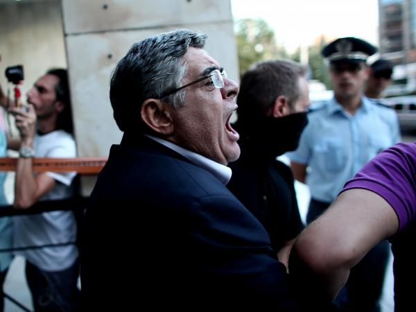The leader of ultra-right wing Golden Dawn party Nikos Michaloliakos is escorted by masked police officers from the police headquarters in Athens on Saturday.