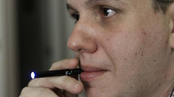 Galen Kipe puffs on an electronic cigarette in Ashboro, N.C., in August.