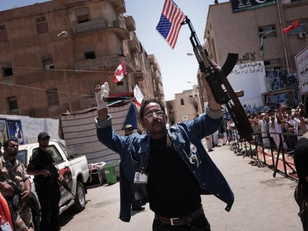A Libyan raises his AK-47 and an American flag in the rebel-stronghold city of Benghazi.