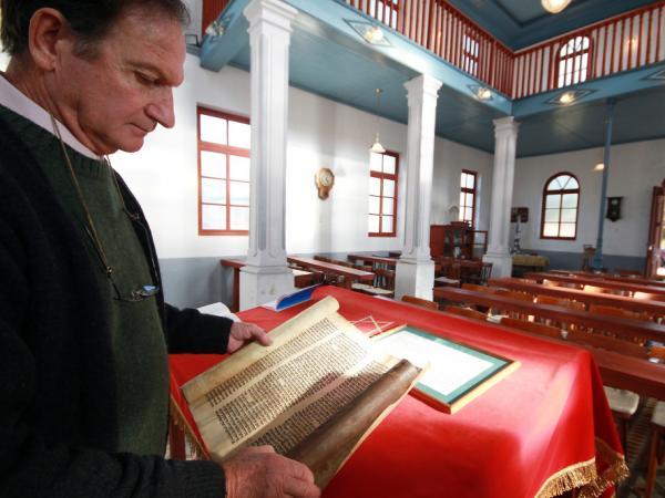 Abraham Kreiserman, the president of the Jewish community of Villa Clara, shows a portion of a Torah scroll at Beth Iacob Synagogue in Villa Clara.
