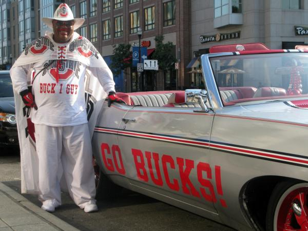 "John Chubb, aka Buck I Guy, standing next to his vintage 1970 Chevy Impala — his ""Buck I Guy Mobile."""