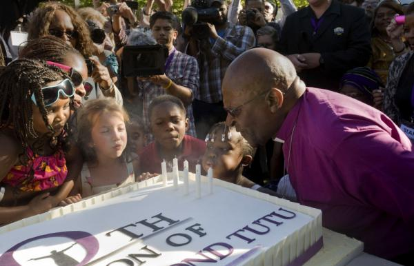 <p>Children help retired Archbishop Desmond Tutu blow out candles on a cake during a celebration of his 80th birthday in Stellenbosch, South Africa, on Friday. </p>