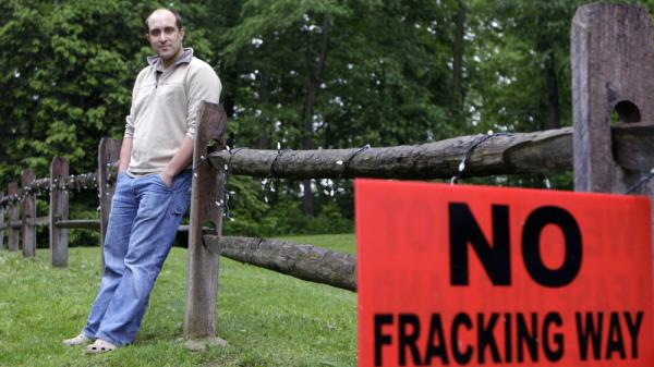 <p>T.J. Turner stands in his yard in Yellow Springs, Ohio, on May 27 near a sign protesting the practice of fracking, a process used to extract oil or natural gas from hard rock formations. Turner was approached by a salesman for an energy exploration company to lease rights for drilling on his property.</p>