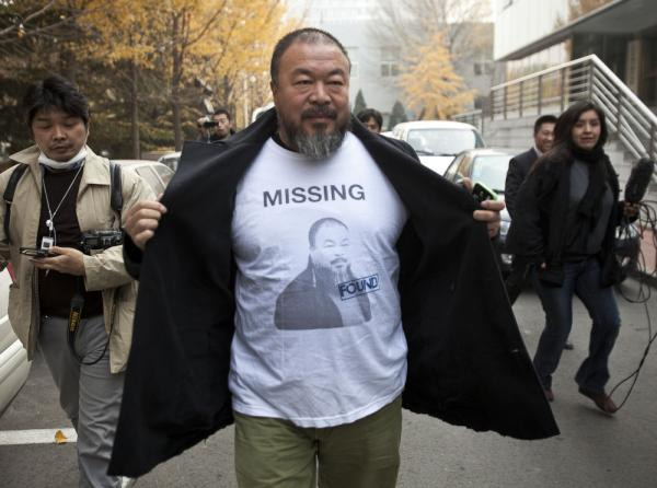 Chinese dissident artist Ai Weiwei opens his jacket to reveal a shirt bearing his portrait as he walks into the Beijing Local Taxation Bureau.