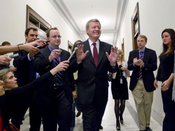 Senate Finance Committee Chairman Sen. Max Baucus, D-Mont., a member of the congressional supercommittee on the deficit, fends off reporters as he arrives to meet in the Capitol Hill office of Sen. John Kerry, D-Mass., on Monday.
