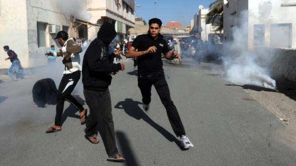 Bahraini protesters run for cover after police fired tear gas canisters to disperse them during a demonstration in the village of Diraz, northwest of Bahrain, Feb. 14. A special commission issued a report Wednesday that found excessive force was used during a crackdown on an anti-government movement that began in February.