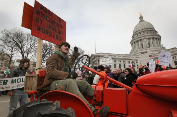 A farmer drives his tractor past the Wisconsin State Capitol during a rally in March.