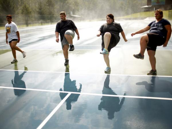 Wellspring students do high steps on the tennis court. Exercise is paramount at Wellspring, and a little rain doesn't get in the way of outdoor activities.
