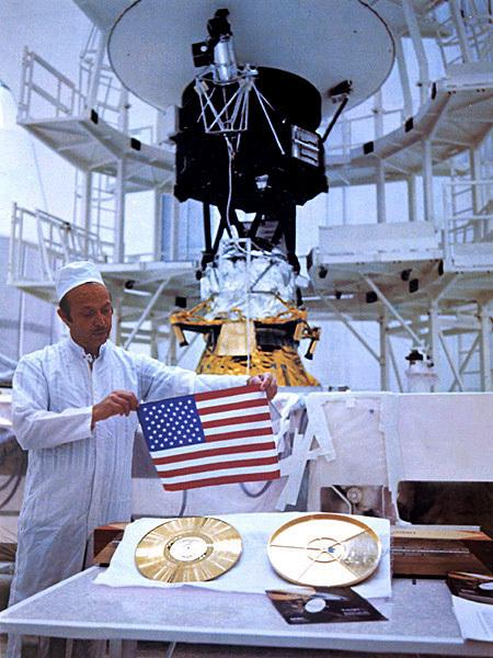 A technician holds a U.S. flag over a gold record containing data from Earth, with a Voyager spacecraft in the background.