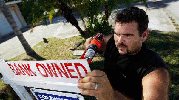 Renzo Salazar, from Real Signs of Ace Post Holding Inc., placed a bank owned sign on top of a for sale sign outside a foreclosed home in Miami last month.