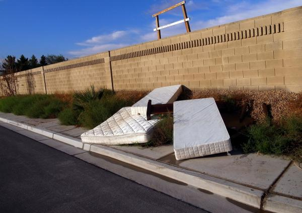 Old mattresses lie on the street outside abandoned homes in Las Vegas, in this 2010 photo. Used mattresses present a unique problem to landfills and recycling firms alike.