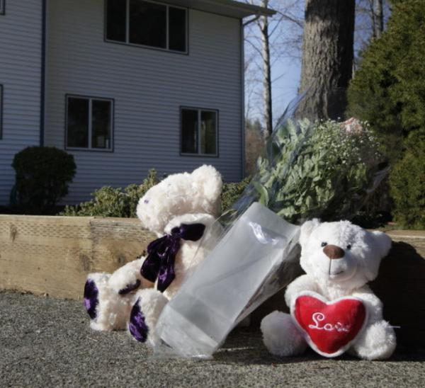 Toys and flowers have been left outside the Puyallup, Wash., home of Chuck and Judy Cox, the grandparents of Charlie and Braden Powell.