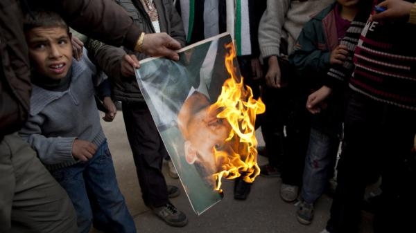 A man burns a portrait of Syrian President Bashar Assad during a Sunday demonstration on the outskirts of Idlib in northern Syria.