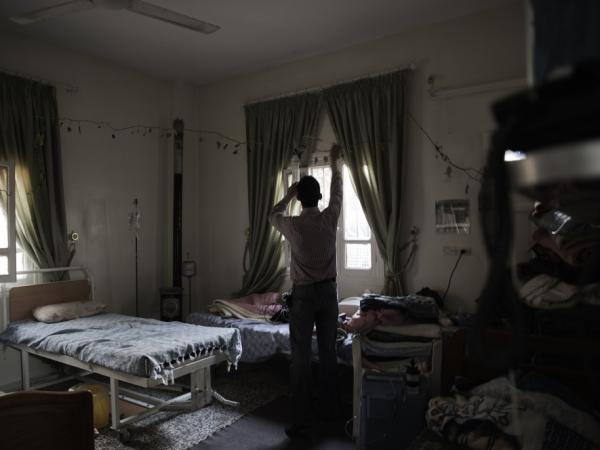 A Syrian man stands in a makeshift surgery room at a private house being used as a hospital in Qusayr, nine miles from Homs.
