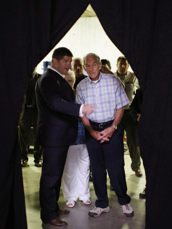 Texas Rep. Ron Paul (right) talks with the his presidential campaign manager, Jesse Benton, backstage at the Republican Party's Iowa straw poll last August.