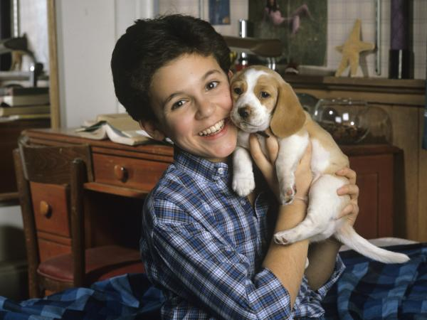 The face you may remember: Fred Savage cuddles up with a puppy on <em>The Wonder Years</em>, in a photo from December 1989.