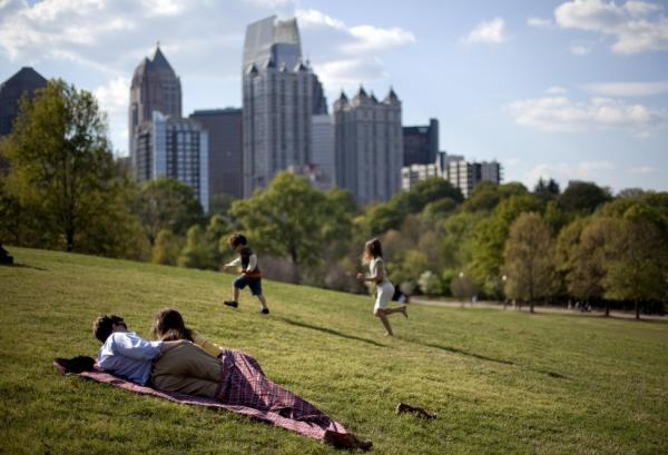 A couple enjoy a sunny afternoon against the backdrop of the Midtown skyline from Piedmont Park in Atlanta in late March.