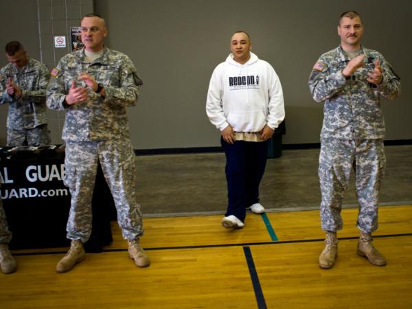 Barillaro (center), of Vallejo, Calif., is introduced to a roomful of new recruits at the National Guard Armory in Evansville, Ind. First Sgt. Larry Lightburne (right), who organized a performance by Barillaro at the armory, heard about the rapper through his wife, who found his lyrics comforting while he was stationed in Iraq.