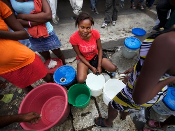 Marlene Lucien controls the hose that fills people's plastic buckets on one busy street corner in Port-au-Prince, Haiti.