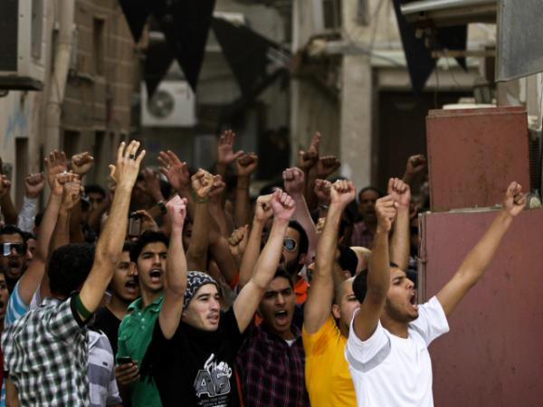 Anti-government protesters chant slogans in Manama, Bahrain, on Thursday. Security forces have fanned out to prevent demonstrators from disrupting Sunday's Formula One race.