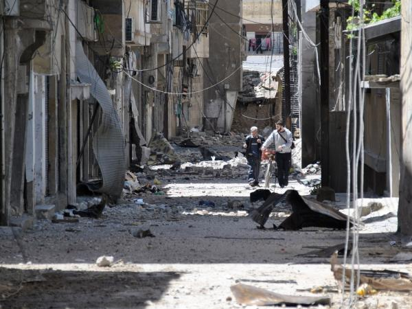 Syrians walk in an alley damaged by Syrian army shelling in the Bab Sbaa neighborhood in Homs province, central Syria, on April 21.