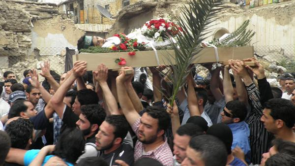 Mourners carry the body of activist Nour Hatem Zahra, 23, during his funeral procession, in Damascus, Syria, on Monday. Friends and fellow activists say Zahra, who posted anti-government graffiti all around the Syrian capital, bled to death after being shot by Syrian security forces on Sunday.