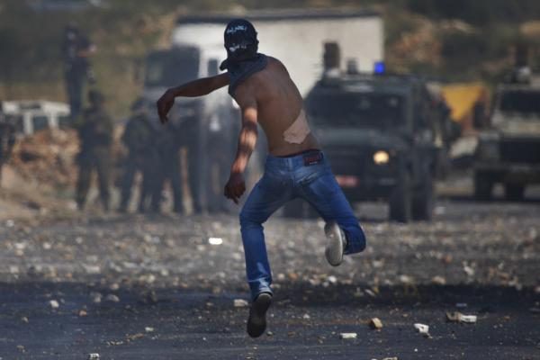 A masked Palestinian hurls a stone at Israeli troops during clashes outside the Ofer military prison, near the West Bank city of Ramallah on Tuesday, amid<em> nakba</em> demonstrations.