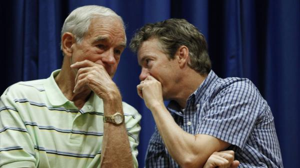 Rep. Ron Paul, R-Texas, and his son, Sen. Rand Paul, R-Ky., talk at a campaign event for the elder Paul in Des Moines, Iowa, last August.