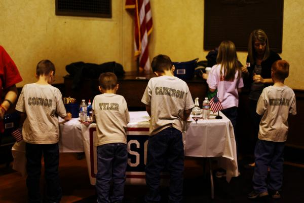 Connor, 10, Tyler, 7, Cameron, 9, Keegan, 9, and Hannah Butt, 10, decorate welcome home signs for their father, Jon, at the welcome home ceremony for the National Guard's 182nd Infantry Battalion in Melrose, Mass.