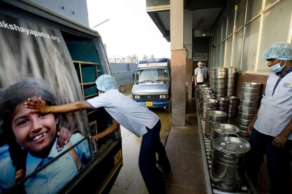 A workman closes the door of an Akshaya Patra truck filled with fresh school lunches. Some 34 trucks head out from this kitchen every school day, providing lunch for nearly 150,000 children in the Bangalore area.