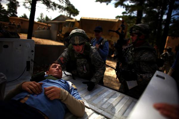 A U.S. soldier puts a wounded Afghan policeman in to the back of a truck after he was shot during a mock gun battle.
