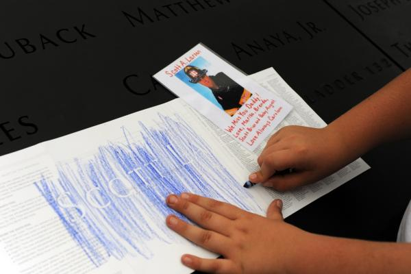 August Larsen, 9, makes a rubbing of his father's name from panels bearing the names of Sept. 11 victims at the 9/11 Memorial.