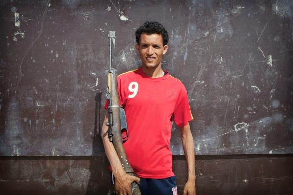 A Libyan rebel poses with his antique bolt-action rifle. He said that it was an American-made 1911; it is actually an Italian-made Carcano. That rifle was most widely used during World War II but can still be found in use in western Libya.