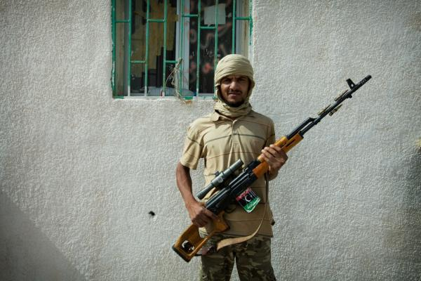 A rebel soldier stands with his battle rifle at the Dahiba border crossing between Libya and Tunisia.