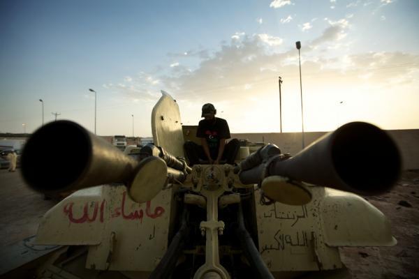 "A rebel fighter loads ammunition into a ZSU-23 ""Shilka"" self-propelled anti-aircraft gun in Zintan."