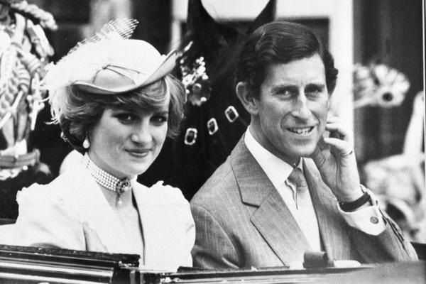 Prince Charles and Diana, Princess of Wales, wearing a coral silk dress and matching hat, ride in a carriage to Waterloo Station to start their honeymoon on July 29, 1981.