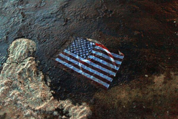 On April 20, 2010, the Deepwater Horizon oil drilling rig exploded in the Gulf of Mexico, setting off the nation's worst oil spill. An American flag lies in a slick of oil that washed ashore in Gulf Shores, Ala., July 4.