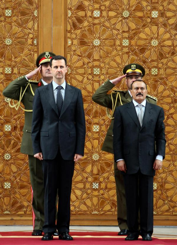 In this photo from 2009, Syrian President Bashar Assad (left) stands with then-Yemeni President Ali Abdullah Saleh during a welcoming ceremony for Saleh at the presidential palace in Damascus. As the violence continues in Syria, the U.S. and other countries are hoping to convince Assad to step down from power, as Saleh did.