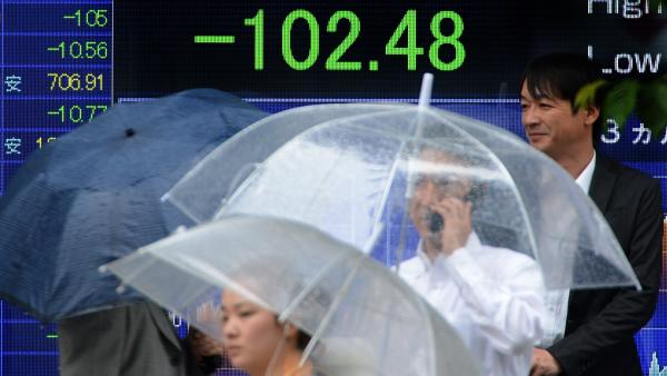 Slow economic growth in the U.S. is having an impact on many countries around the world. Here, people walk past a board flashing the Nikkei index on the Tokyo Stock Exchange in Japan last month.