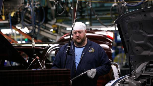 "A worker builds cars on the assembly line at Ford's Chicago Assembly plant, which has adopted the ""three crew"" work schedule. The new third shift can increase efficiency in factories, but it can also wreak havoc on sleep needs and home lives."