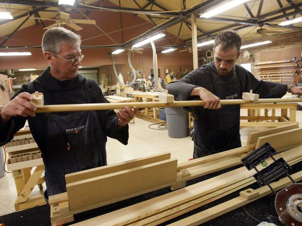 Benedictine Brother Brian Harrington (left) and novice Dustin Bernard pull a casket handle from a press in a workshop at St. Joseph Abbey in Covington, La.