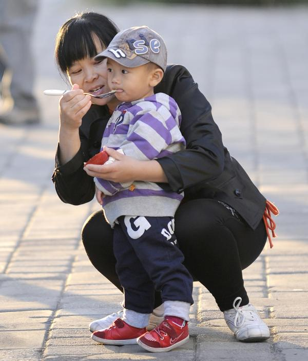 A mother feeds her child in Beijing, Oct. 24, 2011. Experts say many Chinese do not want to have additional children, regardless of official policy.