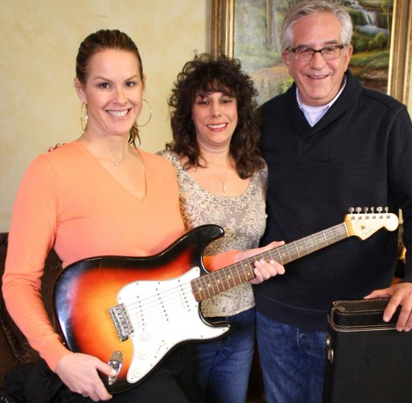 <em>History Detectives</em>' Elyse Luray (left) and Wes Cowan (right), with Dawn Peterson and the guitar Bob Dylan may or may not have played in '65. Peterson says her father came into possession of the famous instrument.