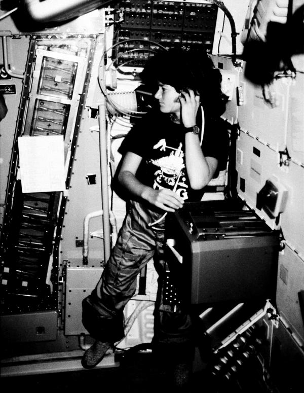 Astronaut Sally K. Ride, STS-7 mission specialist, communicates with ground controllers from the mid-deck of the earth-orbiting Space Shuttle Challenger in June 1983.