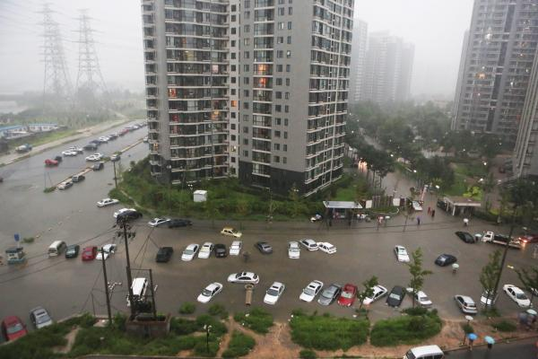Cars are submerged in floodwaters around a residential block in Beijing.