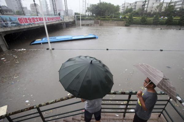 Residents look at a submerged bus on a flooded street amid rainfall in the Tianjin on Thursday. A much expected downpour bypassed Beijing Wednesday but battered the neighboring city of Tianjin instead, flooding many downtown streets and submerging vehicles.