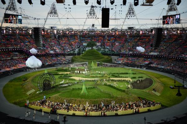Animals and actors enter the stadium for a British meadow scene.