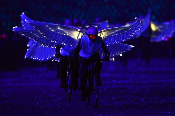Winged performers ride bicycles during the opening ceremony.