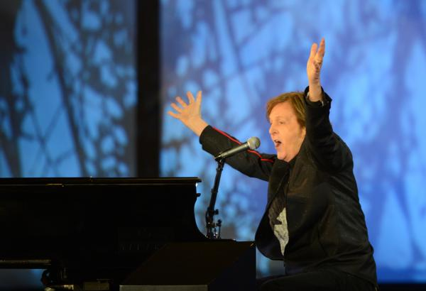 British musician Paul McCartney raises his arms as he sings at the end of the opening ceremony.