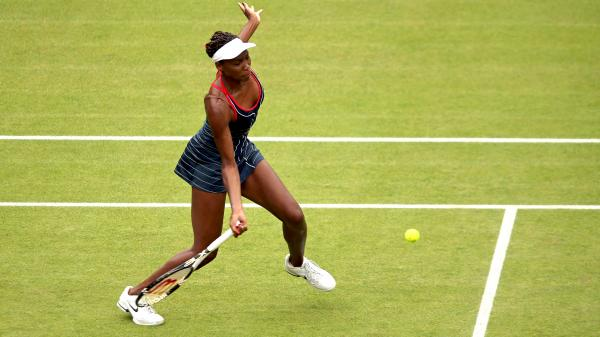 Venus Williams of the United States returns a shot to Aleksandra Wozniak of Canada in their Olympic singles tennis match, played at Wimbledon. Williams won, 6-1, 6-3.